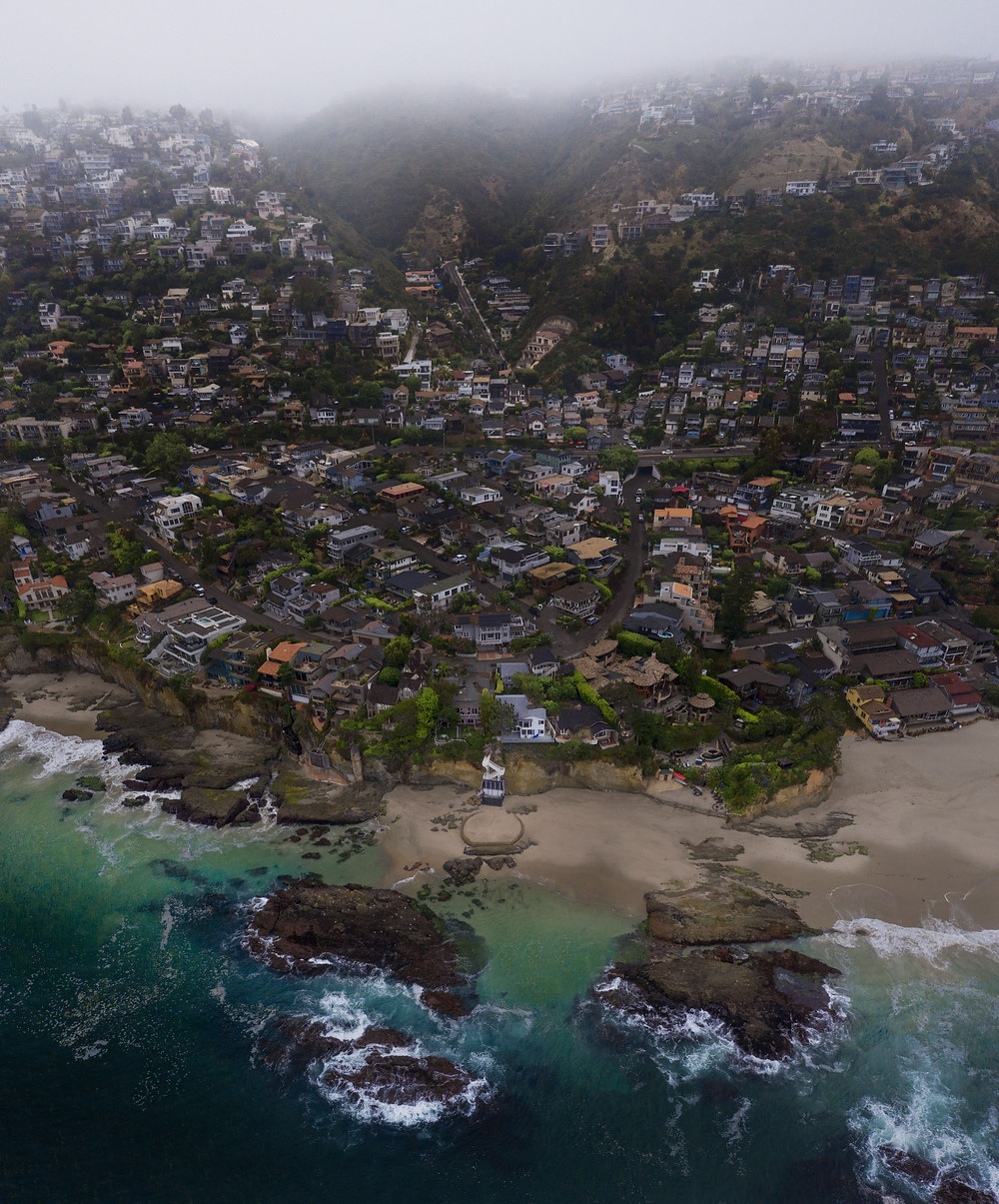 Fog rolling in over the Laguna Beach homes on a hill just above a beautiful beach