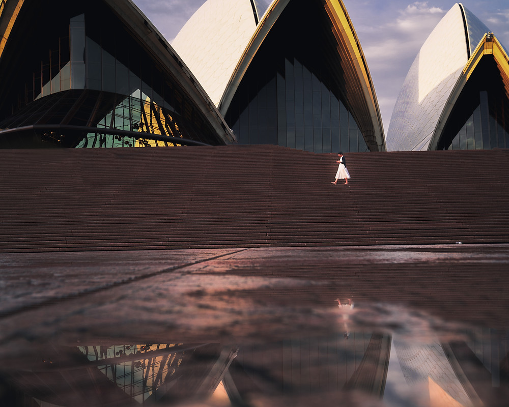 reflection from a puddle of a girl walking along the Sydney Opera House Stairs