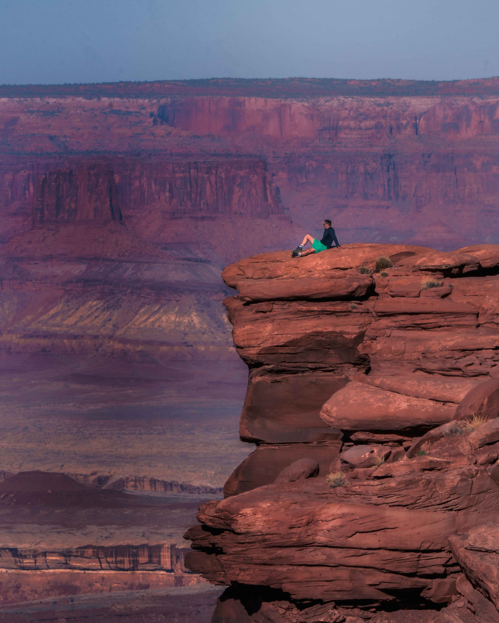 Man sitting on the ledge of the cliff at Canyonlands National Park