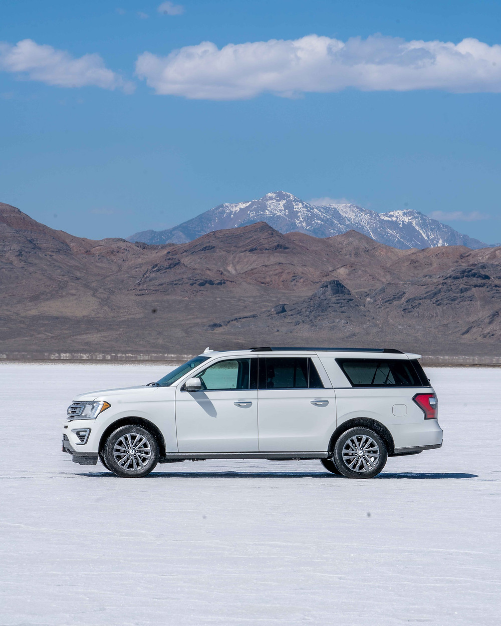 White Ford Expedition in a salt flat with snow capped mountains in the background