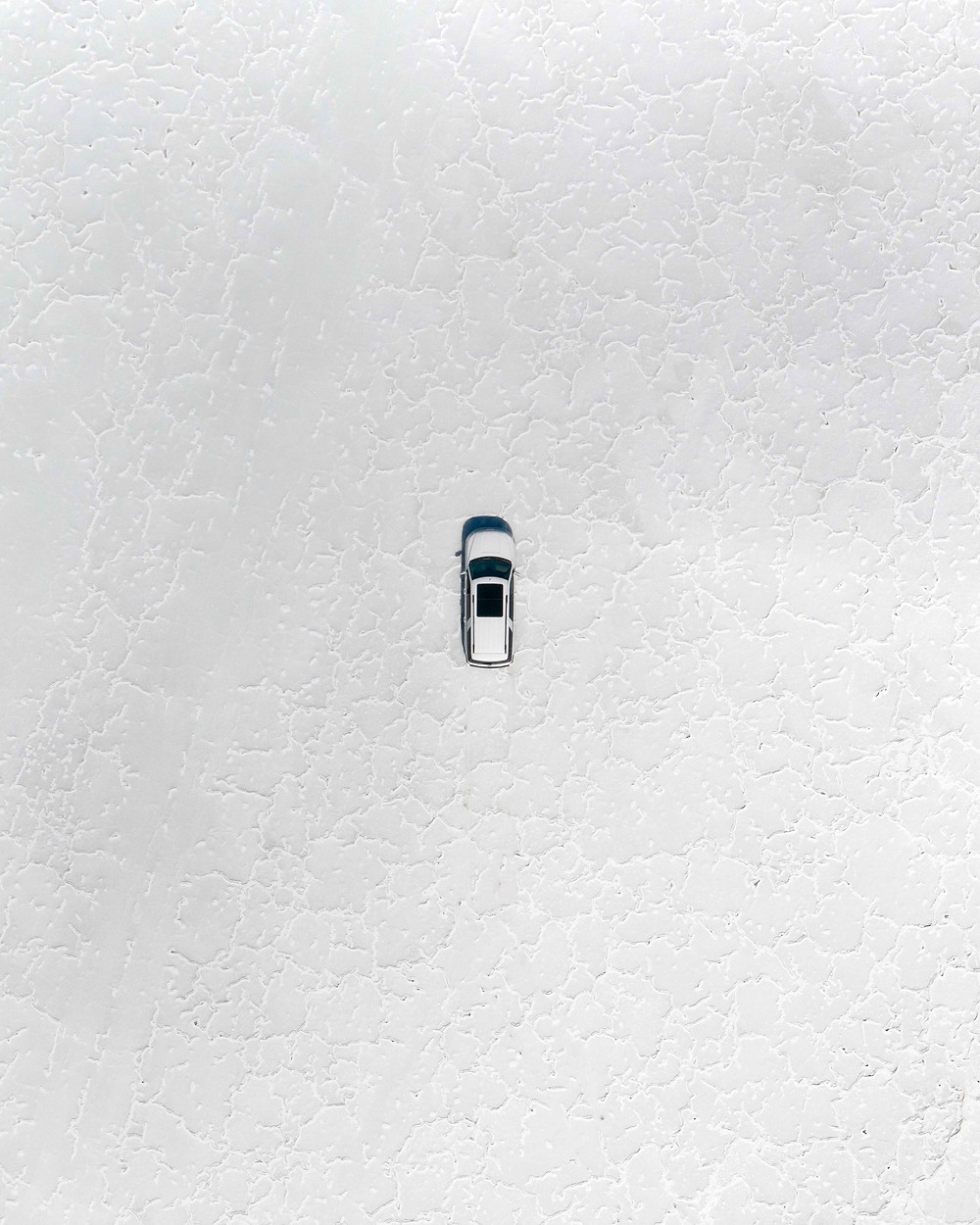 Aerial view of a white truck in the middle of a salt flat