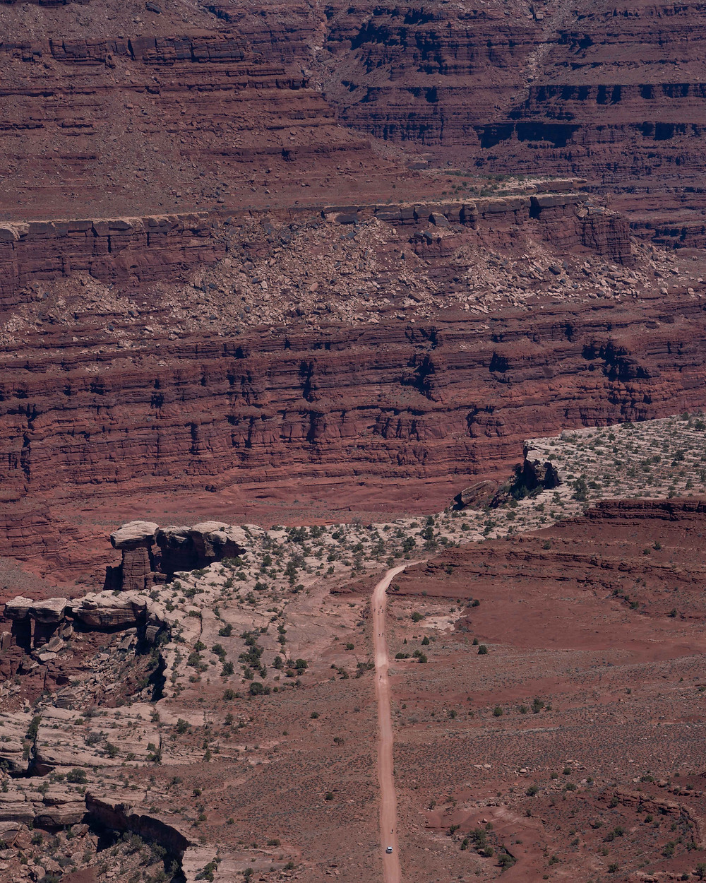 Aerial view of the little cars driving through the shafer dirt trail next to big cliff red mountains