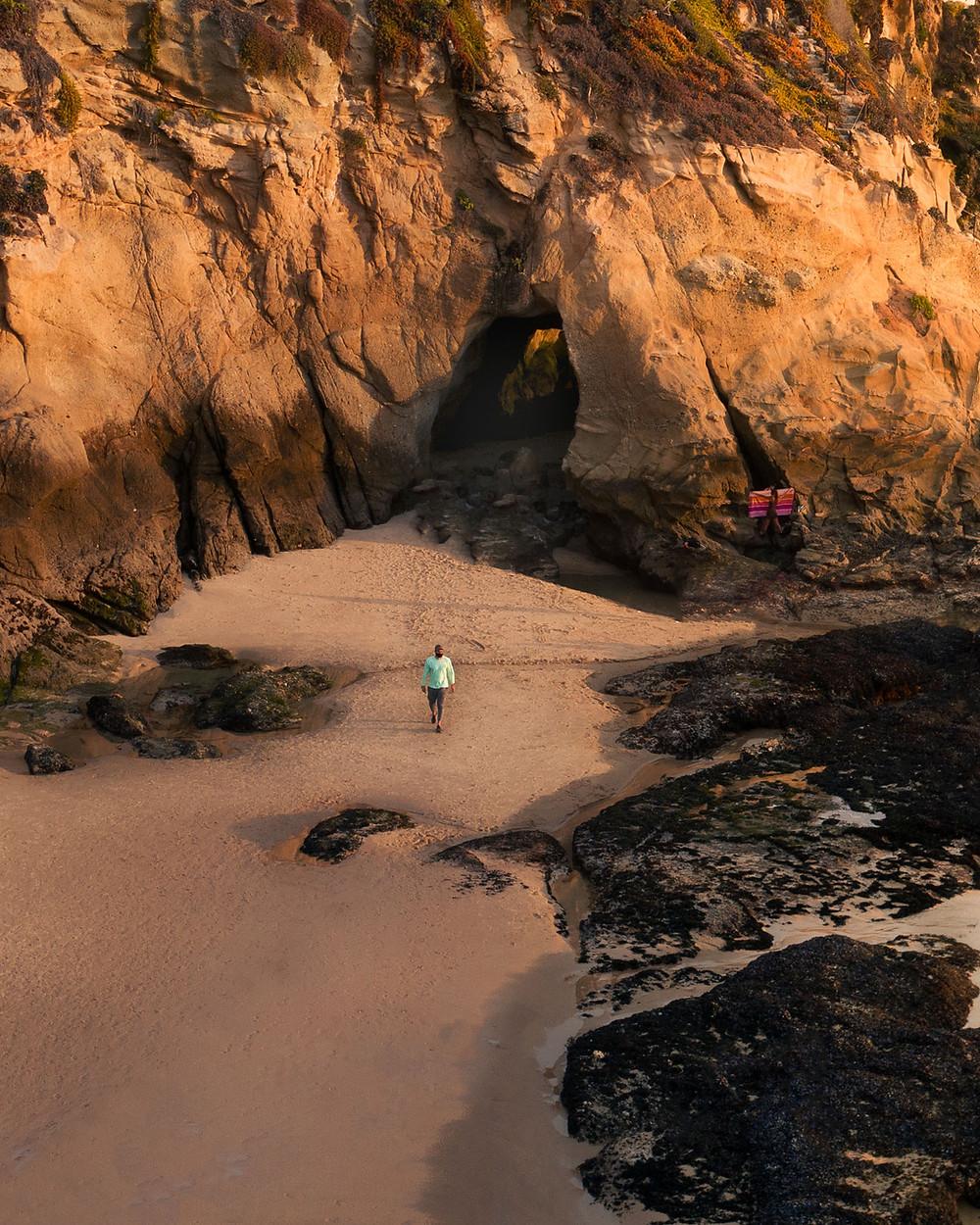 Man leaving a sea cave on a beautiful quiet beach in Laguna Beach