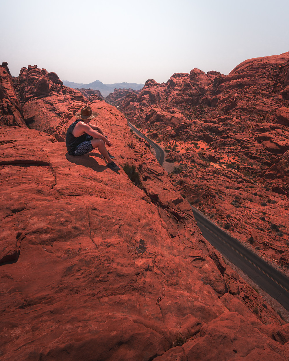 hiker sitting on top of the red rock mountains