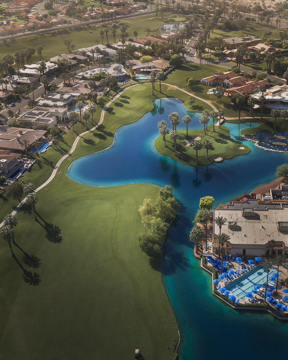Aerial view of a pristine green golf course and aqua blue surrounding waters at the JW Marriott Desert Springs