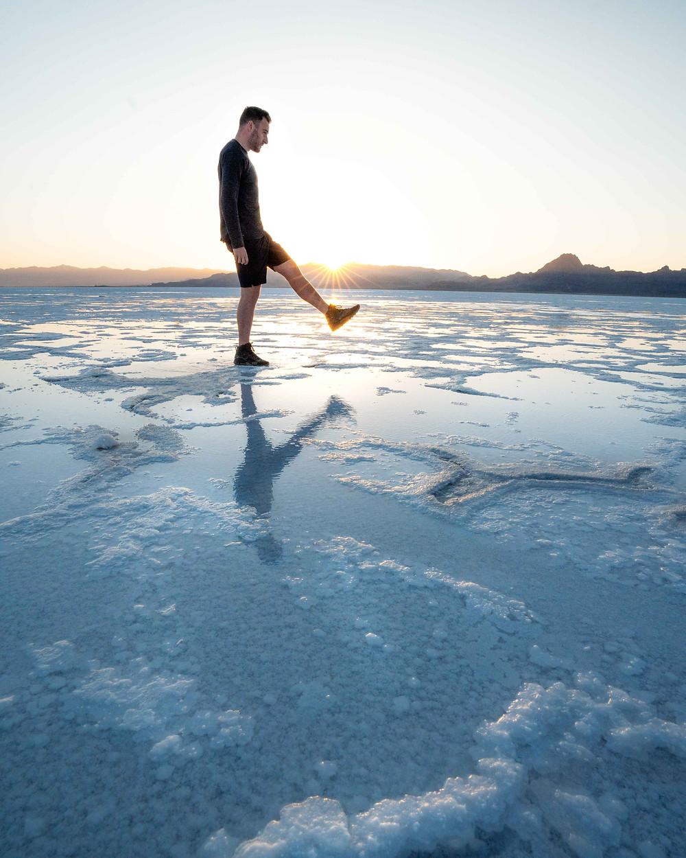hiker kicking a sun burst in the Utah salt flats