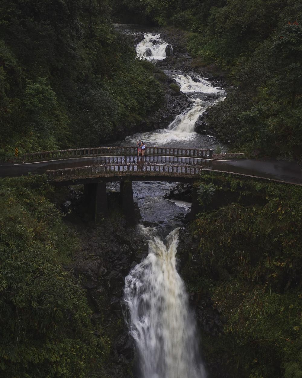 Couple standing on a bridge overlooking waterfalls on the road to Hana