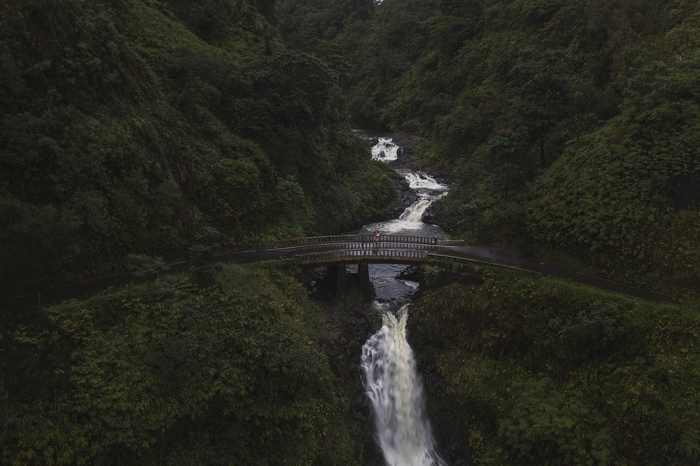 A couple standing on a bridge over a waterfall in Maui