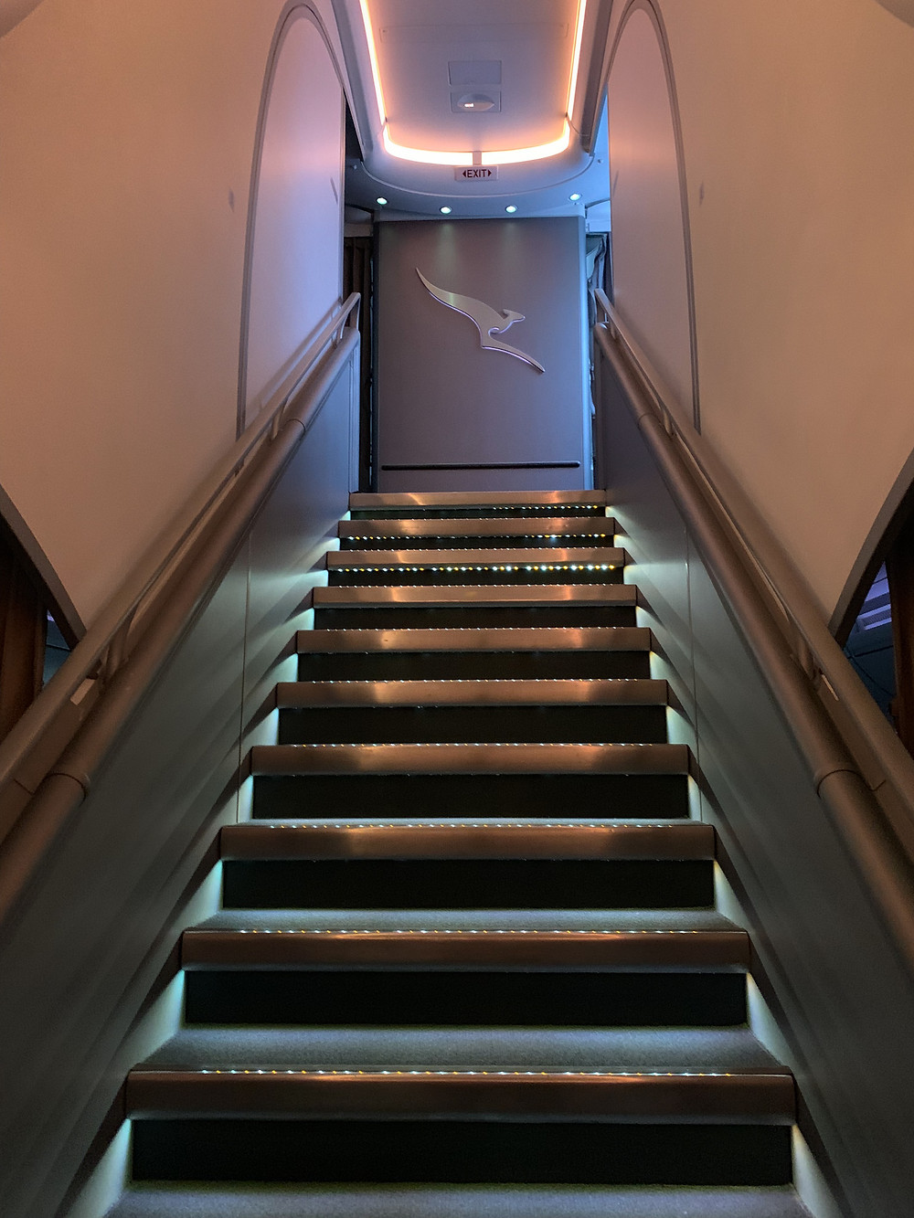 Staircase looking up on the Qantas Airbus A380 featuring the iconic airline logo