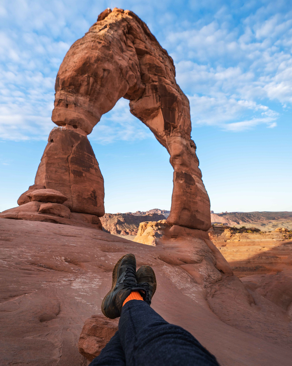 hiker resting in front of the delicate arch