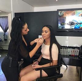 Makeup artist applies makeup to model