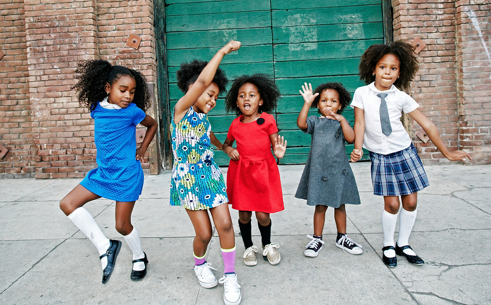 Group of young African American girls dancing in the street