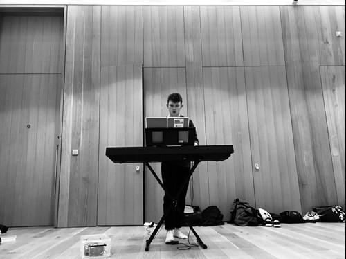 Josh stands behind a keyboard with the score of Made in Dagenham on the stand