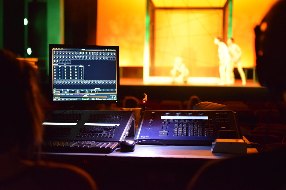 The lighting desk is in the foreground, on stage actors and a large cube monopolise the image
