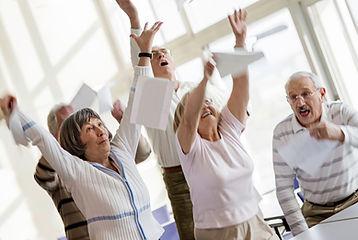 Glada pensionärer höja händerna