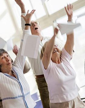 Séniores felizes que levantam as mãos