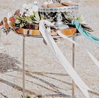 cake pedestal on round natural wood tabl