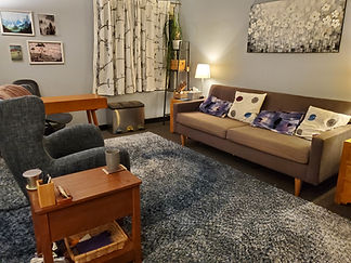 A therapy office full of blue, purple, and grey furniture and decor