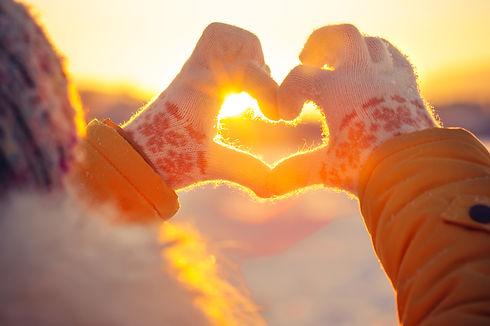 Woman hands in winter gloves Heart symbo