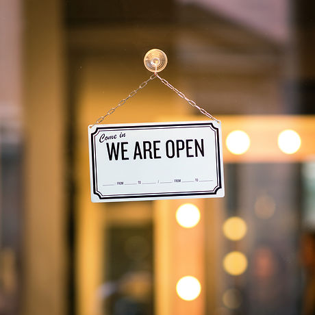 WE ARE OPEN sign board through the glass