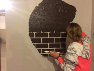 Kate Paints the brick in the wall