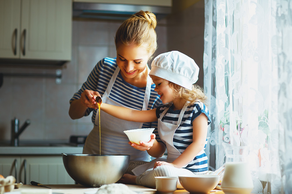 family time in the kitchen with mother and small daughter cooking