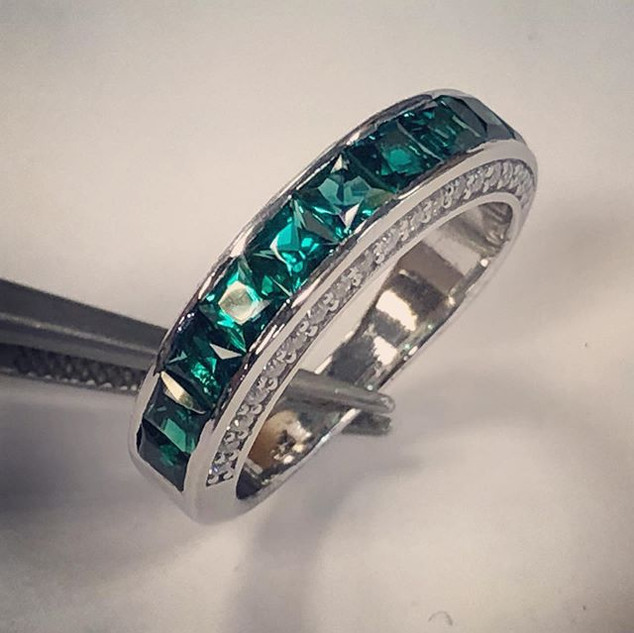 Emerald and diamond band in white gold .
