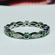 Wedding band with diamond and tsavorites