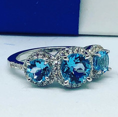 Blue topaz three stone ring in halo offs
