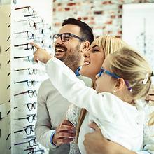 Happy family choosing glasses in optics