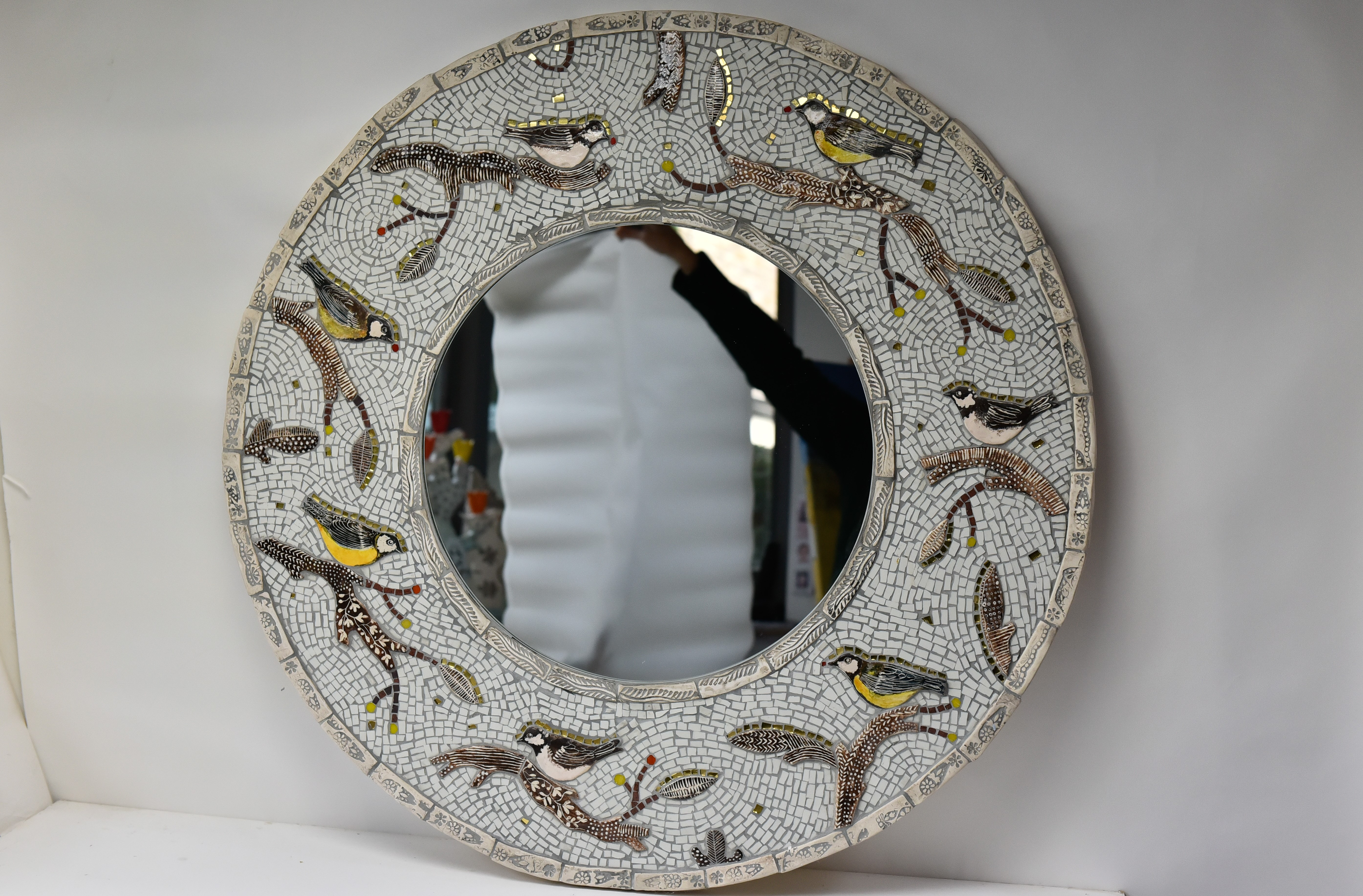 round mosaic mirror with gold rimmed bir