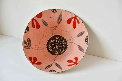 pink bowl with black and red leafy desig