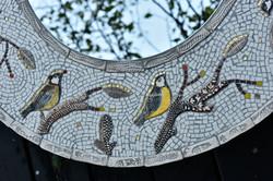 round mosaic mirror with gold rimmed bir