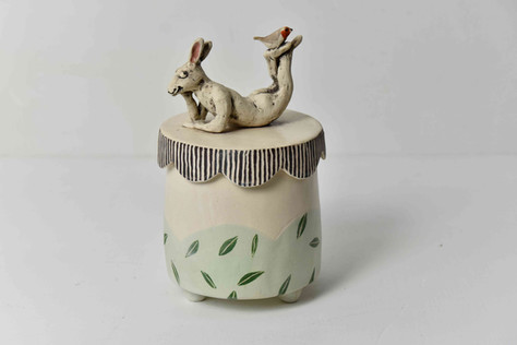 small box with resting hare with robin
