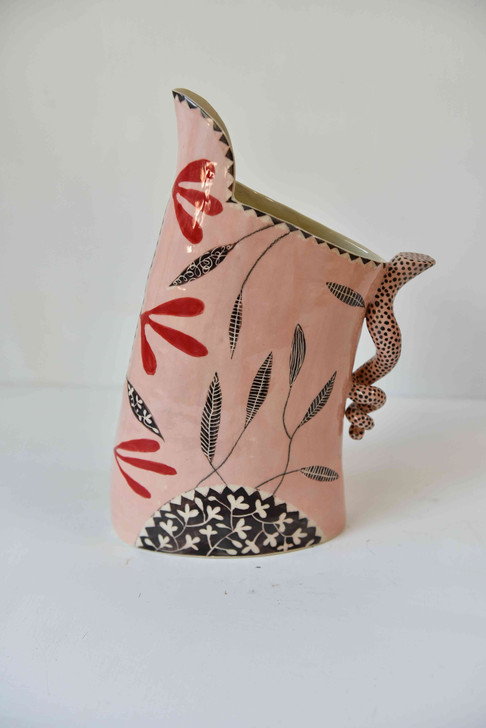 pink jug with black and red leaf design, spotted handle