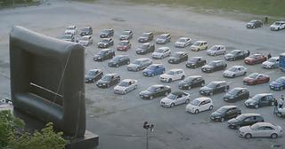 In Zeiten von Corona wurde auch in Bielefeld im Sommer 2020 ein Autokino veranstaltet. Die tri-ergon film- & werbeagentur war mit dabei. Hier zu sehen eine Aufnahme aus der Luft von Autos vor der aufgestellten Leinwand.