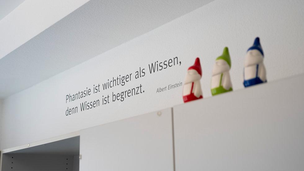 """RGB Farbende Zwerge neben dem Schriftzug: """"Phantasie ist wichtiger als Wissen, denn Wissen ist begrenzt."""" von Albert Einstein"""