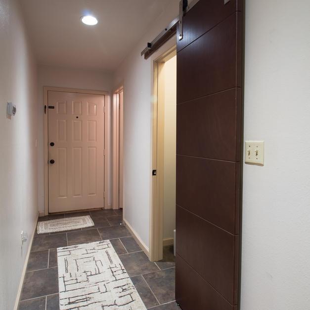Barn door to coat closet, front door & ba.