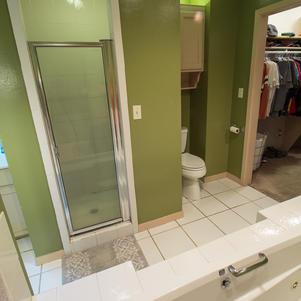 Walk-in tiled shower w/ seat.