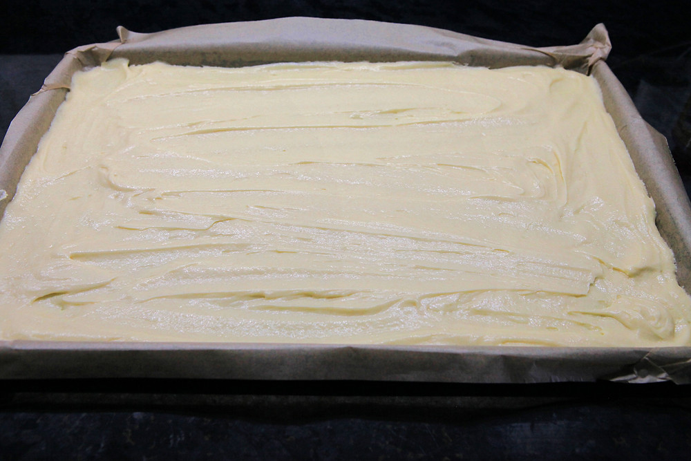 Spread batter evenly in the baking tray