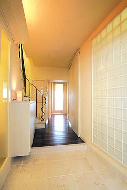 アールの壁とガラスブロックのあしらいで、ゆったりとした印象の玄関が誕生