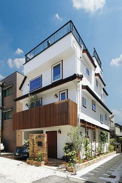 スイス漆喰の白壁に、イペ材のバルコニーフェンスが映える3階建ての住まい