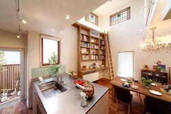 オリジナルデザインのキッチンと大きな壁面本棚はHさんのお気に入り