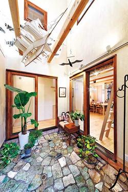 吹抜けの土間玄関は、リビングに光と風を導き、広がりをもたらす中庭の役割も