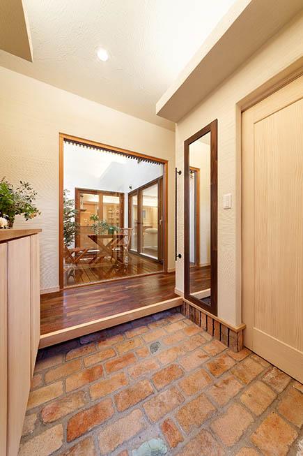 アンティークレンガ敷きの玄関から、中庭越しにLDKの温もりが感じられる