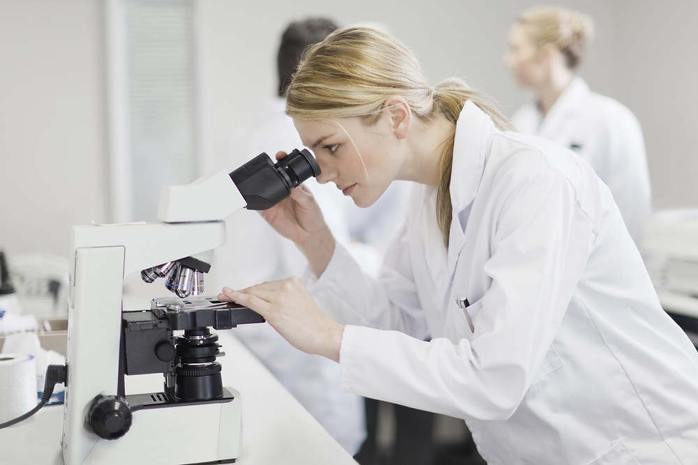 A scientists looking through microscope