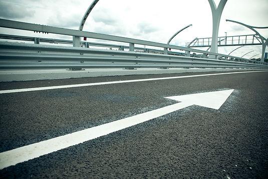 Bilden föreställer en nymålad vit pil och linjemålning på en bro.