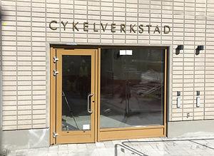 På en ljus tegelfasad är det monterat fasadbokstäver i mässing som bildar ordet CYKELVERKSTAD. Nedanför skylten är det ett glasparti och en entrédörr till cykelverstaden.