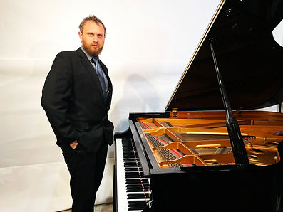 Copy of Tim Chernikoff standing at piano.jpg
