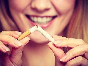 Smilling woman breake down cigarette. Wi